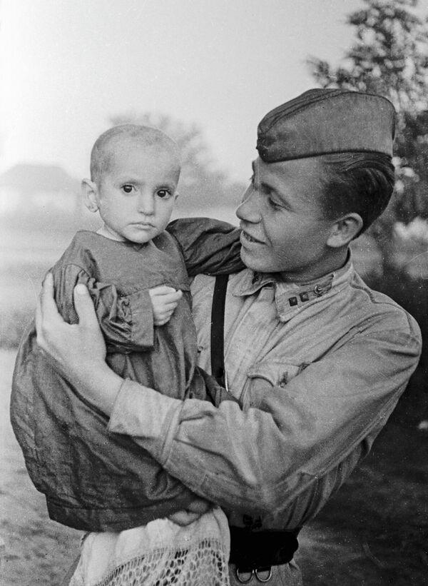 Советский офицер держит на руках спасённую им девочку из деревни Эльхотово