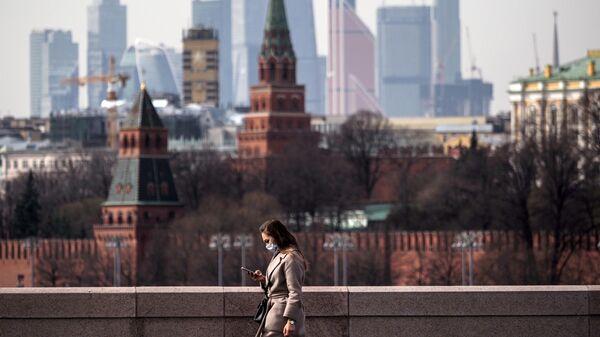 Девушка в медицинской маске во время прогулки в Москве