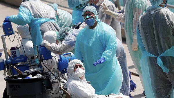 Сотрудники службы быстрого реагирования эвакуируют больных членов экипажа с двух круизных лайнеров Costa Favolosa и Costa Magica в порту Майами, США