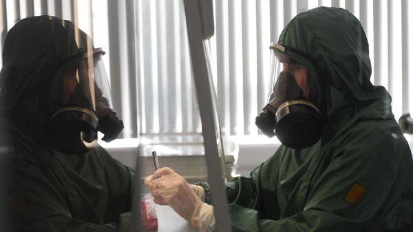 Сотрудник за работой в вирусологической лаборатории