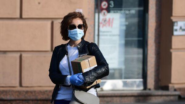 Девушка в медицинской маске и перчатках на улице Москвы