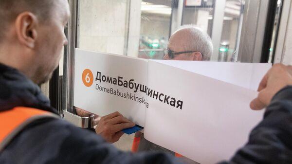 Сотрудник метрополитена приклеивает на двери стикер ДомаБабушкинская