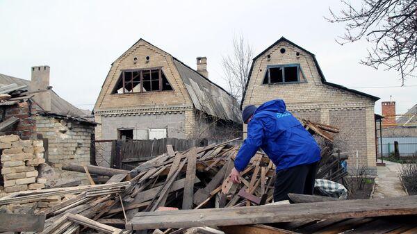 Местный житель во дворе частного дома, разрушенного после ночного артобстрела по Петровскому району Донецка