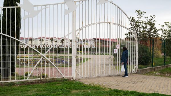 Женщина читает объявление о закрытие орнитологического парка в Сочи