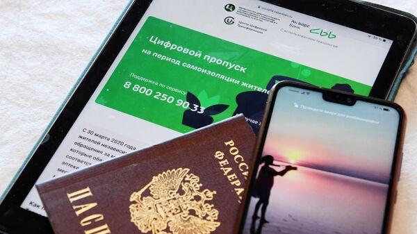 Паспорт, планшет и смартфон, позволяющие получить цифровой пропуск через смс для выхода из дома в режиме самоизоляции