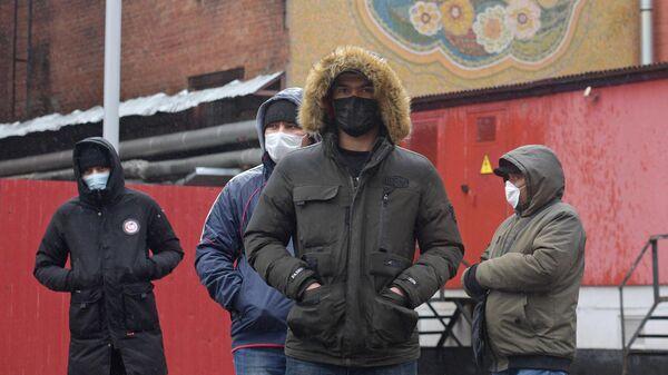 Мигранты стоят у здания Управления Федеральной миграционной службы России