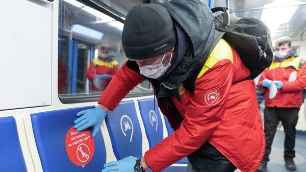 Сотрудник метро наклеивает стикер Держите дистанцию, не садитесь здесь в вагоне московского метрополитена