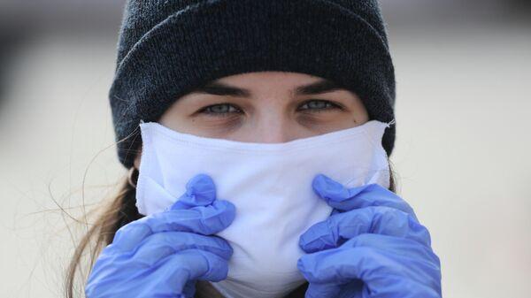 Сотрудница волонтерского центра в Тамбове в защитной маске и перчатках