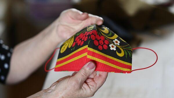 Татьяна Борисова держит в руках дизайнерскую маску в народном стиле