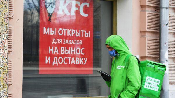 Курьер службы доставки еды Delivery Club стоит в очереди у окна кафе KFC