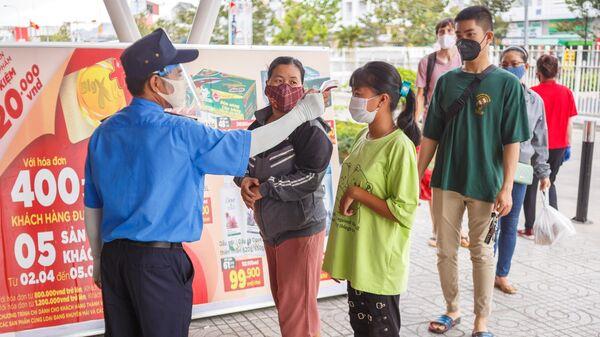 Охранник измеряет температуру у покупателя на входе в супермаркет в курортном городе Нячанг во Вьетнаме