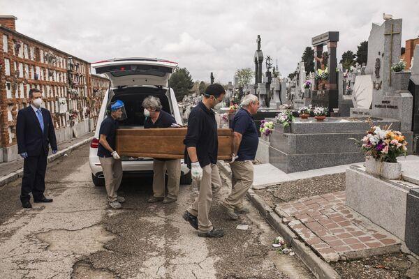 Грузчики несут гроб на кладбище Альмудена в Мадриде