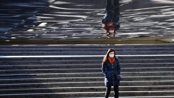 Девушка в защитной маске в подземном переходе на одной из улиц в Москве