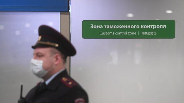 Сотрудник полиции у выхода из зоны таможенного контроля в Международном аэропорту Шереметьево