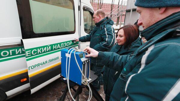 Сотрудники настраивают прибор для забора проб воздуха в Москве