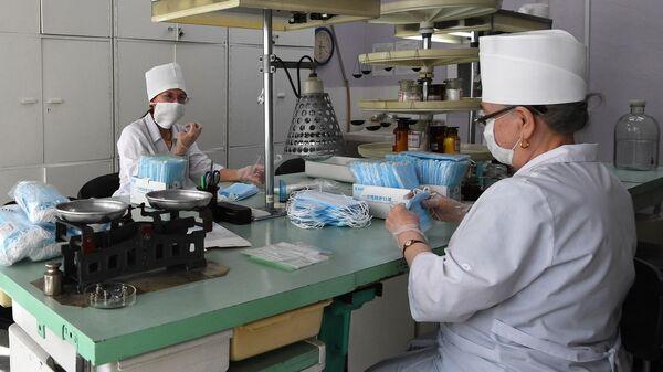 Сотрудницы аптеки в Новосибирске фасуют одноразовые медицинские маски в упаковки