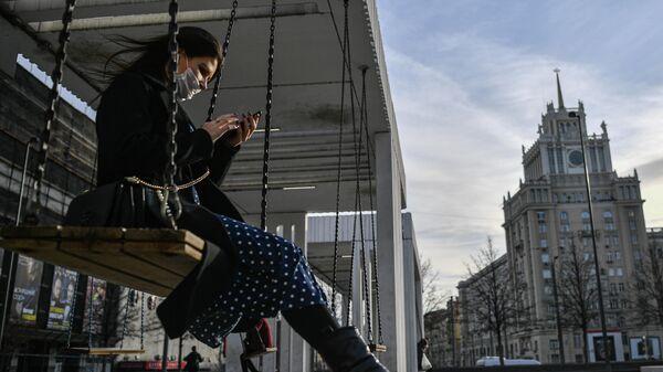 Девушка в защитной маске на Триумфальной площади в Москве