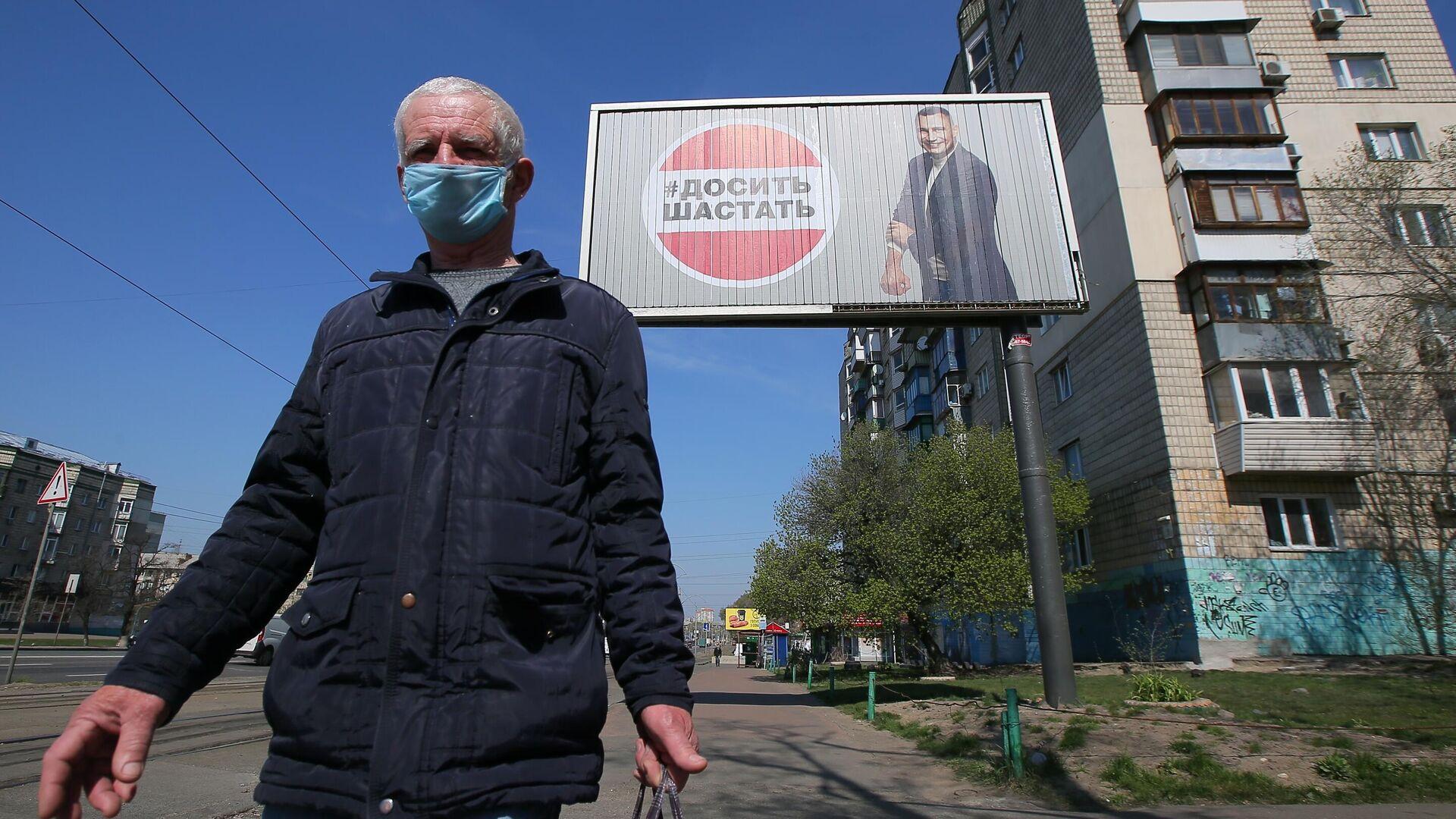 Мужчика в защитной маске у рекламного щита, установленного в Киеве в связи с коронавирусом - РИА Новости, 1920, 13.10.2020
