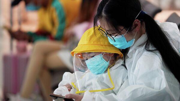 Женщина и ребенок в защитных костюмах в международном аэропорту Ухань Тяньхэ после снятия блокировки города