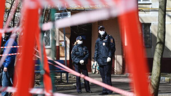 Сотрудники полиции недалеко от огороженной детской площадки в период самоизоляции жителей