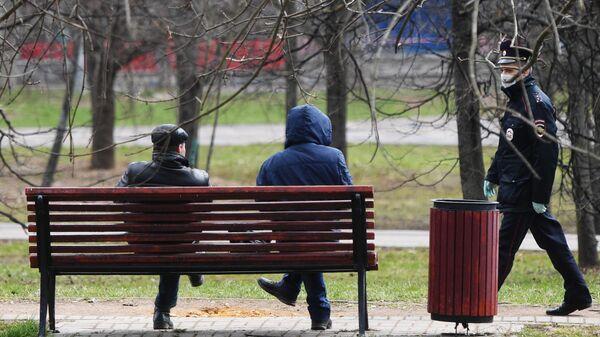 Сотрудник полиции подходит к людям, сидящим на скамейке в сквере