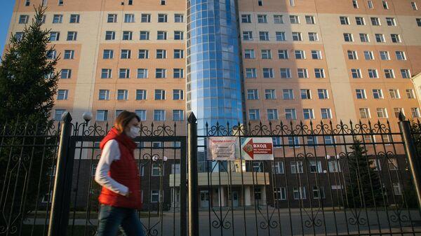 Девушка в защитной маске проходит мимо закрытого входа на территорию республиканской клинической больницы в Уфе
