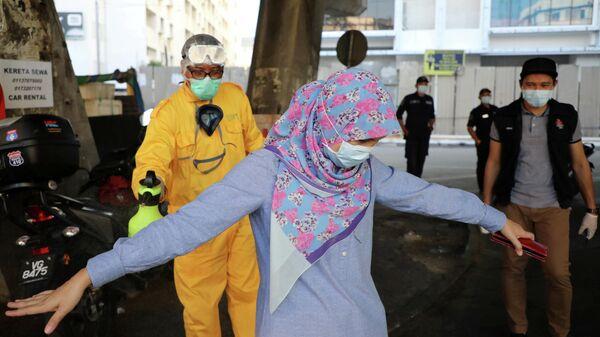 Рабочий распыляет дезинфицирующее средство на женщину  на контрольном пункте за передвижением людей во время эпидемии коронавируса в Куала-Лумпуре, Малайзия