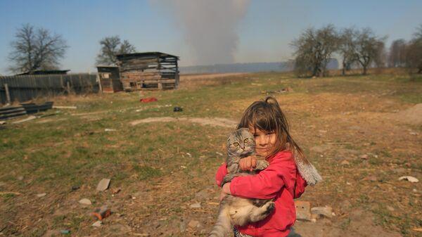 Девочка с котом во дворе частного дома в селе Раговка