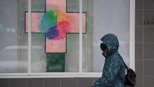 Прохожий в медицинской маске около аптеки в городе Щелково Московской области