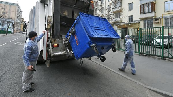 Сотрудники компании Эколайн выгружают мусор из контейнера в мусоровоз в одном из дворов Москвы