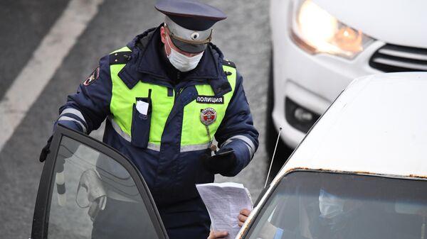 Сотрудник ДПС ГИБДД проверяет электронный пропуск у водителя