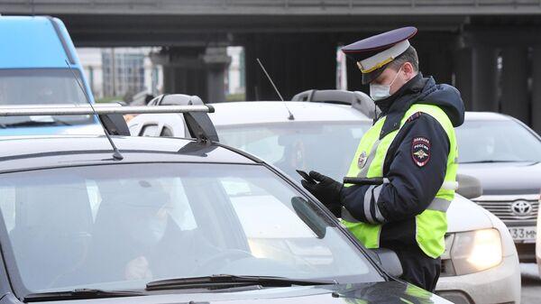 Сотрудник ДПС ГИБДД проверяет электронный пропуск у водителя при въезде в Москву