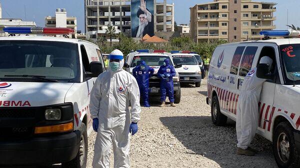 Члены мобилизованных, в рамках программы оказания помощи минздраву Ливана для борьбы с коронавирусом, бригад гражданской обороны Хезболлы у машин скорой помощи в южном Ливане