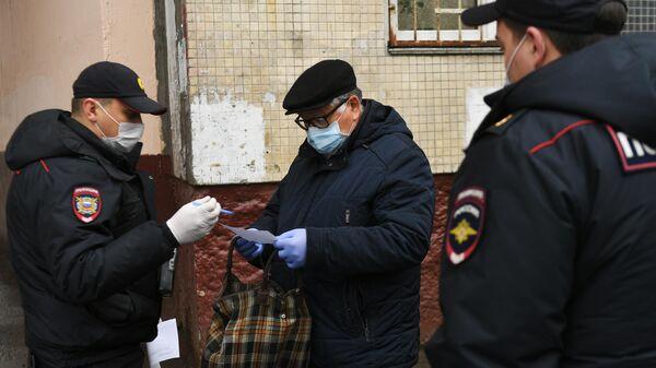 Сотрудники полиции проводят оповещение граждан на одной из улиц в Москве