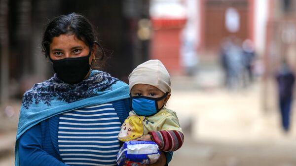 Женщина несет ребенка на руках на окраине Катманду