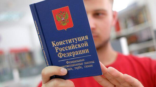 Молодой человек держит Конституцию Российской Федерации