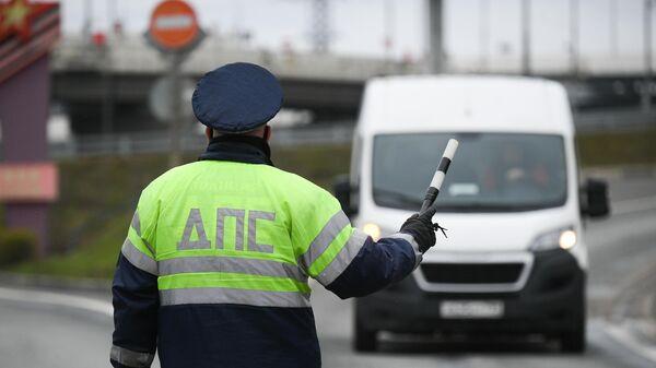 Инспектор дорожно-патрульной службы останавливает водителя для проверки у него цифрового пропуска на передвижение по Москве