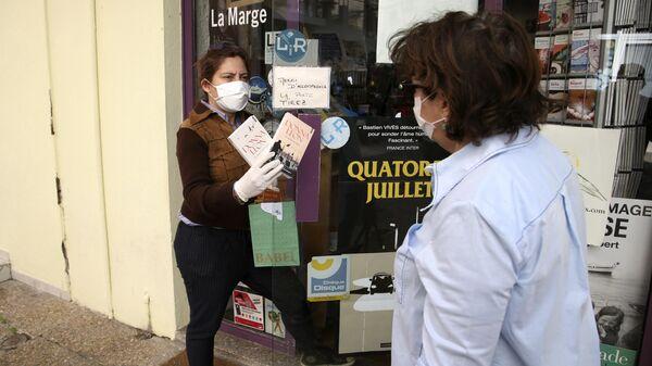 Женщина продает книги возле своего книжного магазина в Аяччо, Корсика, Франция