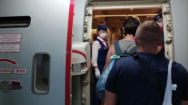 Российские граждане поднимаются на борт самолета авиакомпании Россия в аэропорту Денпасара перед полетом в Москву