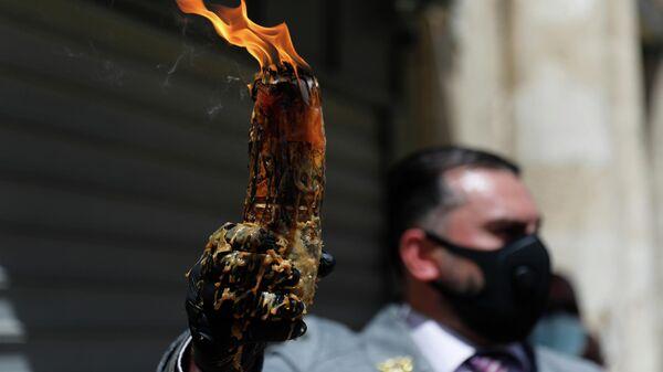 Мужчина в защитной маске держит свечу, зажженную от Благодатного огня в храме Гроба Господня в Иерусалиме