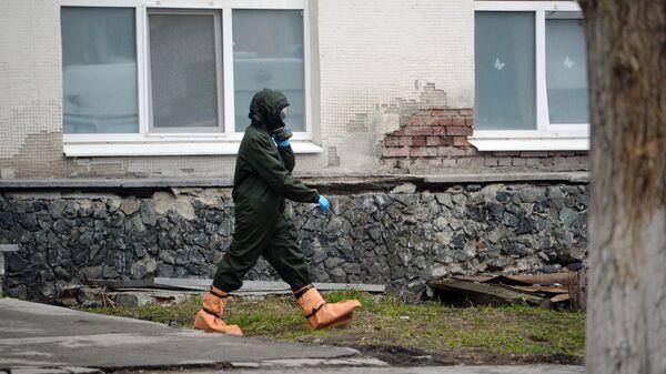 Медицинский работник в защитном костюме у здания Центральной городской клинической больницы № 1 в Екатеринбурге