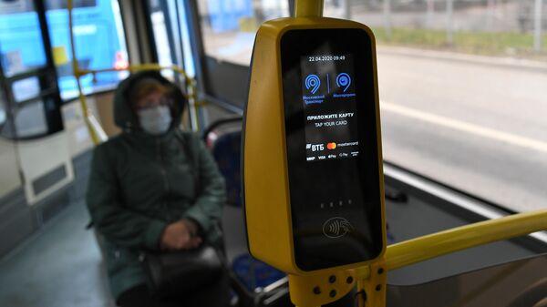 Пассажир в защитной маске в салоне городского автобуса в Москве