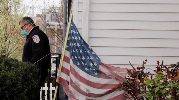 Медик в защитной маске выходит из дома в Эверетте, штат Массачусетс
