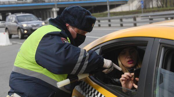 Инспектор дорожно-патрульной службы проверяет у пассажира такси пропуск