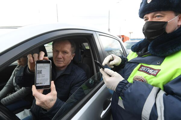 Инспектор дорожно-патрульной службы проверяет у водителя цифровой пропуск на передвижение по Москве