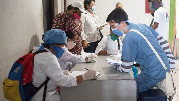 Медики и жители перед тестированием на коронавирус в фавелах Каракаса