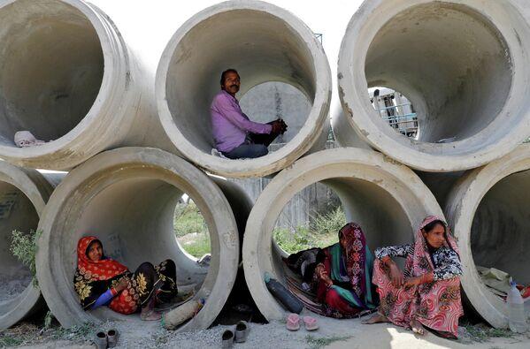 Рабочие-мигранты отдыхают в цементных трубах в Лакхнау, Индия. 22 апреля 2020 года