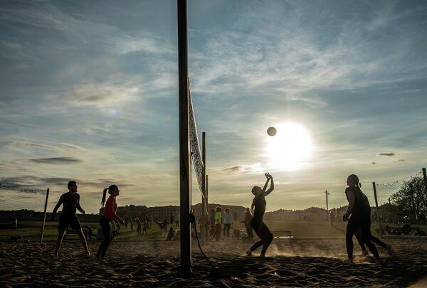 Люди играют в пляжный волейбол в парке в Стокгольме, Швеция