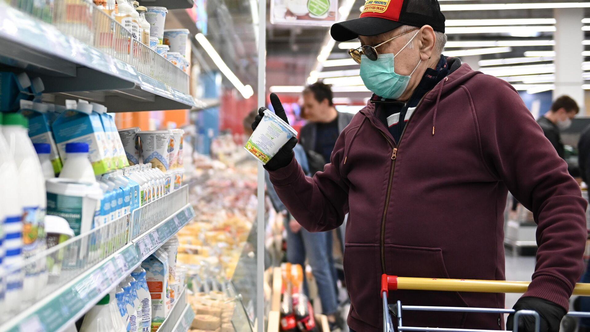 Мужчина в защитной маске покупает продукты в гипермаркете  - РИА Новости, 1920, 10.12.2020