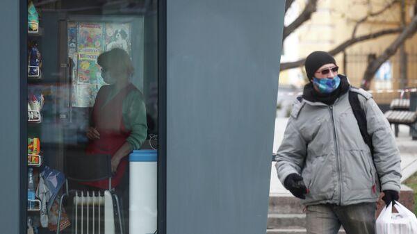Мужчина рядом с торговым киоском на улице Москвы
